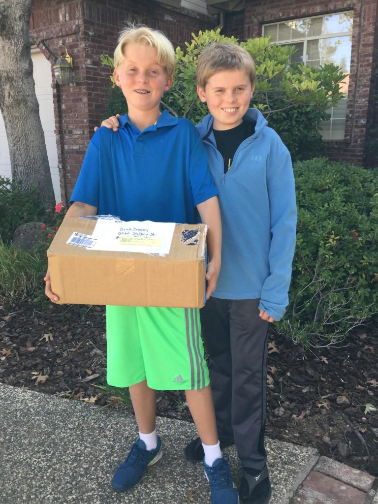 Kyle Rutz and Lleyton Rutz with Schreffler family's LEGO donation to BrickDreams